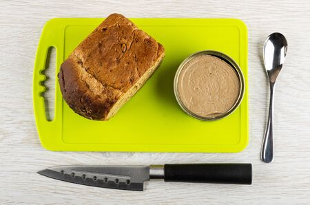 Loaf of bread, metallic jar with liver pate on cutting board, kitchen knife, teaspoon on wooden table. Top view