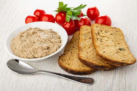 White bowl with liver pate, tomato cherry, parsley, slices of bread, teaspoon on wooden table 写真素材