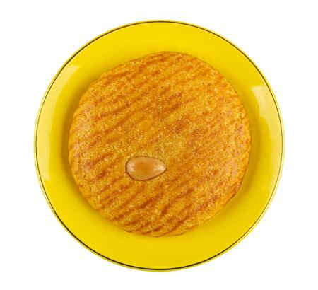 Shortbread with marzipan in yellow saucer isolated on white background. Top view Stock Photo