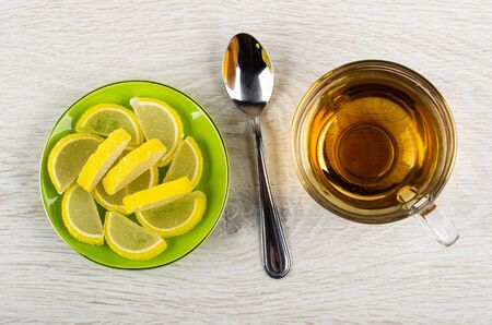 Marmalade in form slices of lemon in green saucer, teaspoon, transparent cup with tea on light wooden table. Top view