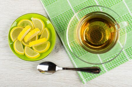 Marmalade in form slices of lemon in green saucer, transparent cup with tea on saucer on napkin, teaspoon on light wooden table. Top view