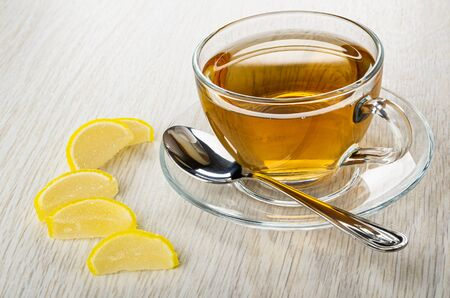 Marmalade in form slices of lemon, transparent cup with tea, teaspoon on saucer on light wooden table
