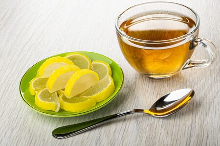 Marmalade in form slices of lemon in green saucer, transparent cup with tea, teaspoon on light wooden table 写真素材