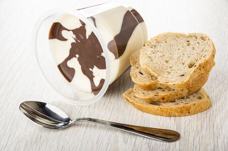 Overturned jar with chocolate-nut paste, slices of bread, spoon on wooden table