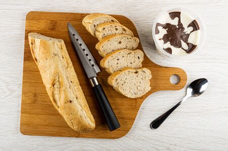 Loaf of bread, slices of bread, kitchen knife on bamboo cutting board, jar with chocolate-nut paste, spoon on wooden table. Top view