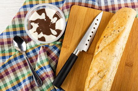 Chocolate-nut paste in jar, loaf of bread and kitchen knife on bamboo cutting board, spoon on checkered napkin. Top view