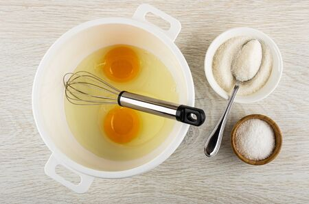 Two broken eggs with yolk, whisk in white plastic pan, spoon in bowl with sugar, bowl with salt on wooden table. Top view