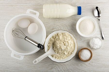 Chicken eggs, whisk in plastic pan, bottle of kefir, bowl with wheat flour, bowls with sugar, soda, salt and spoon on wooden table. Top view
