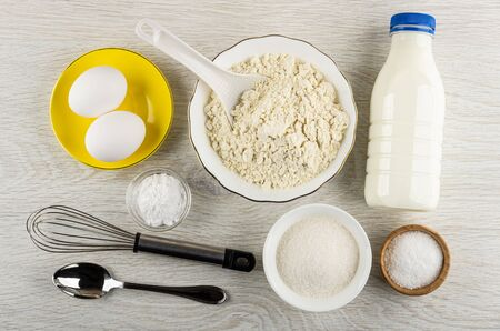 Chicken eggs in saucer, whisk, spoon, bottle of kefir, bowl with wheat flour, bowls with sugar, soda, salt on wooden table. Top view