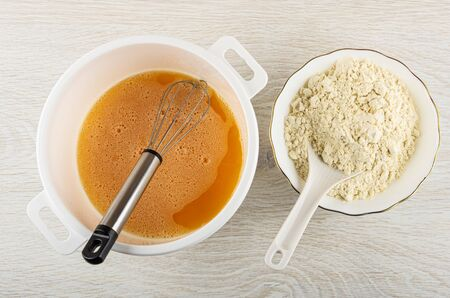 Mix of eggs, sugar and salt with whisk in plastic pan, spoon in bowl with wheat flour on wooden table. Top view Imagens