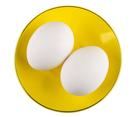 Two chicken eggs in yellow saucer isolated on white background. Top view