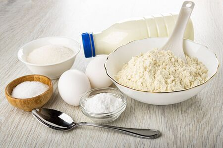Bowl with sugar, bottle of kefir, eggs, bowl with wheat flour, bowls with soda, salt, spoon on wooden table Imagens