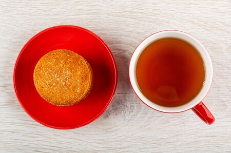 Orange shortbread cookies in red saucer, cup with tea on light wooden table. Top view