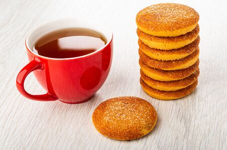 Red cup with tea, stack of orange shortbread cookies, cookie on light wooden table