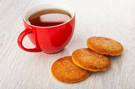 Red cup with tea, three orange shortbread cookies on light wooden table
