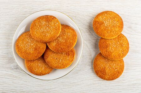 Orange shortbread cookies in white saucer, cookies on light wooden table. Top view