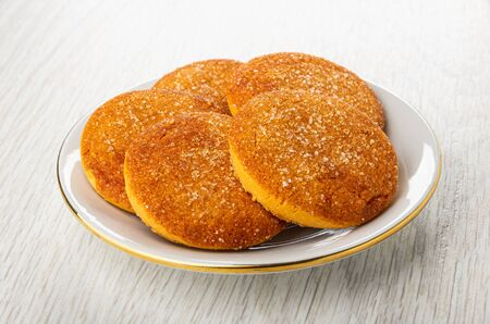 Orange shortbread cookies in white saucer on light wooden table