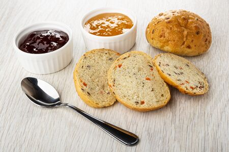 Bowls with jam, teaspoon, bun with cereal, slices of bun on light wooden table