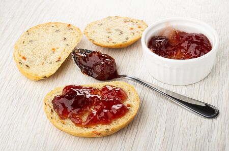 Bowl with strawberry jam, spoon with jam, sandwich with jam on light wooden table Imagens