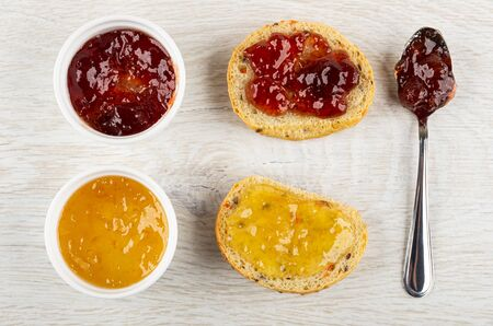 Bowls with jam, teaspoon with jam, sandwiches with jam on light wooden table. Top view