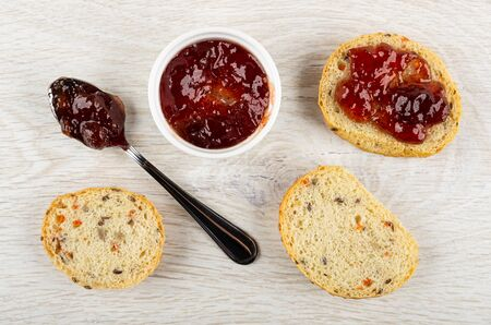 Bowl with strawberry jam, spoon with jam, slices of bun, sandwich with jam on light wooden table. Top view