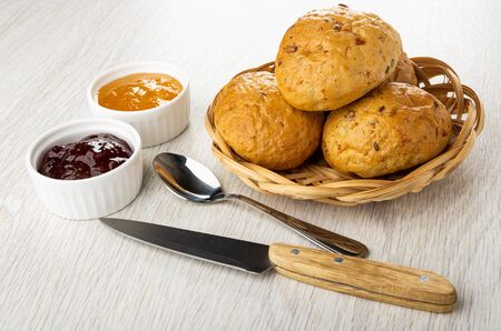 Bowls with jam, teaspoon, kitchen knife, buns with cereal in wicker basket on light wooden table Imagens