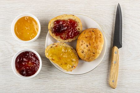 Bowls with strawberry jam and lemon jam, sandwiches with jam, bun in saucer, kitchen knife on light wooden table. Top view