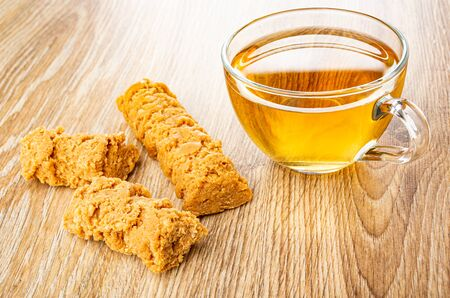 Pieces of creamy-peanut sausages, transparent glass cup with tea on wooden table
