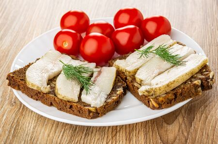 Tomatoes cherry, two sandwiches with salted pork lard and dill in white plate on wooden table