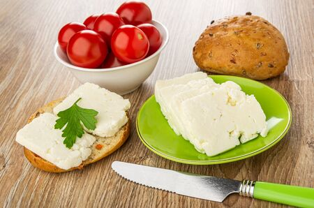 Bowl with tomato cherry, small bun, slices of soft cheese in green saucer, sandwich with cheese and parsley, knife on wooden table
