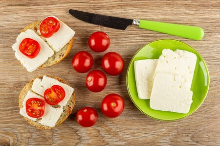 Two sandwiches with soft cheese and tomato cherry, tomatoes, table knife, slices of cheese in green saucer on wooden table. Top view