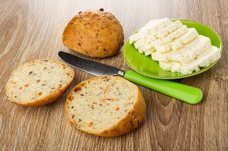 Small bun, pieces of bread, slices of soft cheese in green saucer, table knife on wooden table Zdjęcie Seryjne
