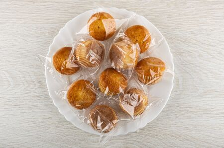 Small muffins in transparent package in white dish on wooden table. Top view