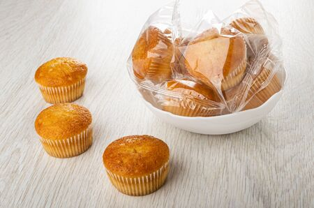 Small muffins in transparent package in white bowl, muffins on wooden table