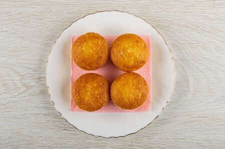 Four small muffins on pink paper napkin in white plate on wooden table. Top view