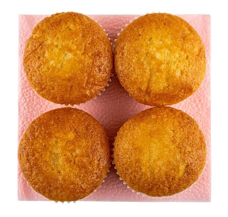 Four small muffins on pink paper napkin isolated on white background. Top view Stock Photo
