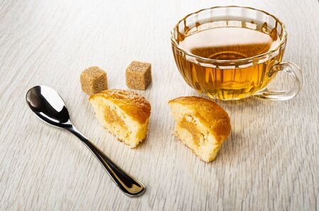 Sugar cubes, teaspoon, halves of small muffin with cream, transparent cup with tea on wooden table