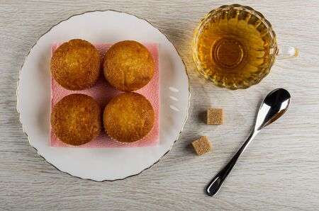 Four small muffins on pink paper napkin in white plate, cup with tea, sugar cubes, teaspoon on wooden table. Top view