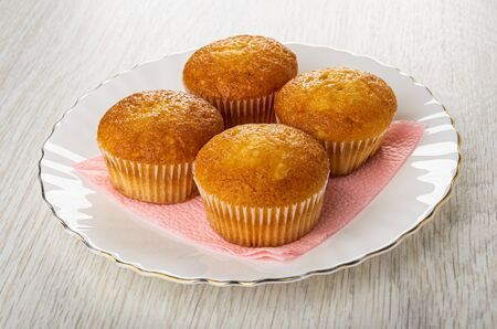 Four small muffins on pink paper napkin in white plate on wooden table Stock Photo