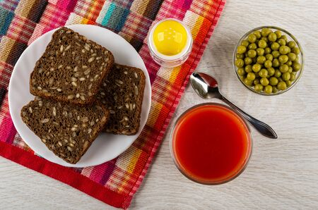 Rye bread with sunflower seeds in white plate, salt shaker on checkered napkin, glass with tomato juice, bowl with green peas, teaspoon on wooden table. Top view