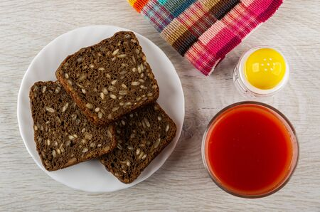 Rye bread with sunflower seeds in white plate, checkered napkin, salt shaker, glass with tomato juice on wooden table. Top view Stock Photo