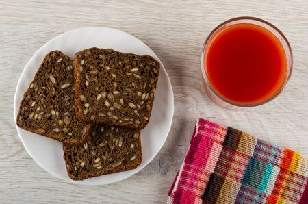 Rye bread with sunflower seeds in white plate, glass with tomato juice, checkered napkin on wooden table. Top view