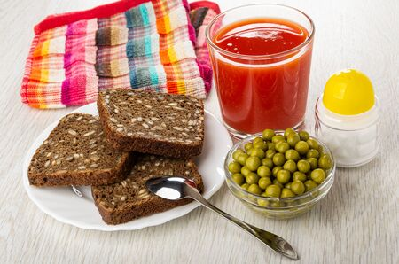 Checkered napkin, rye bread with sunflower seeds in white plate, teaspoon, glass with tomato juice, salt shaker, bowl with green peas on wooden table