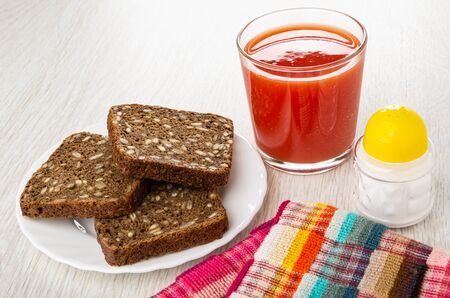 Rye bread with sunflower seeds in white plate, glass with tomato juice, salt shaker, checkered napkin on wooden table