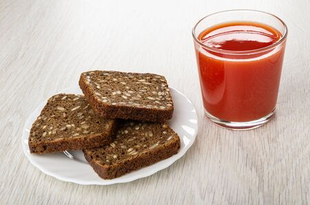 Rye bread with sunflower seeds in white plate, glass with tomato juice on wooden table