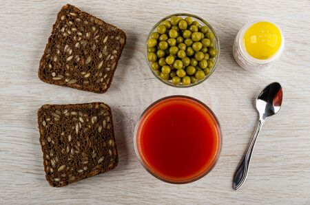 Pieces of rye bread with sunflower seeds, bowl with green peas, salt shaker, glass with tomato juice, teaspoon on wooden table. Top view