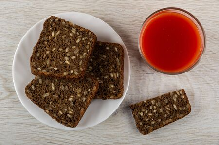 Rye bread with sunflower seeds in white plate, piece of bread, glass with tomato juice on wooden table. Top view
