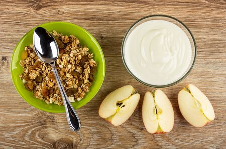 Spoon in green bowl with granola, transparent bowl with yogurt, pieces of apple on wooden table. Top view