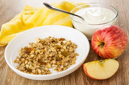 Yellow napkin, transparent bowl with yogurt, spoon, granola in white plate, whole apple and piece of apple on wooden table Reklamní fotografie