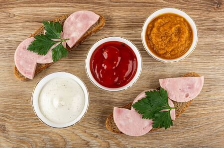 Sandwiches with sausage and parsley, bowls with squash caviar, ketchup and mayonnaise on wooden table. Top view